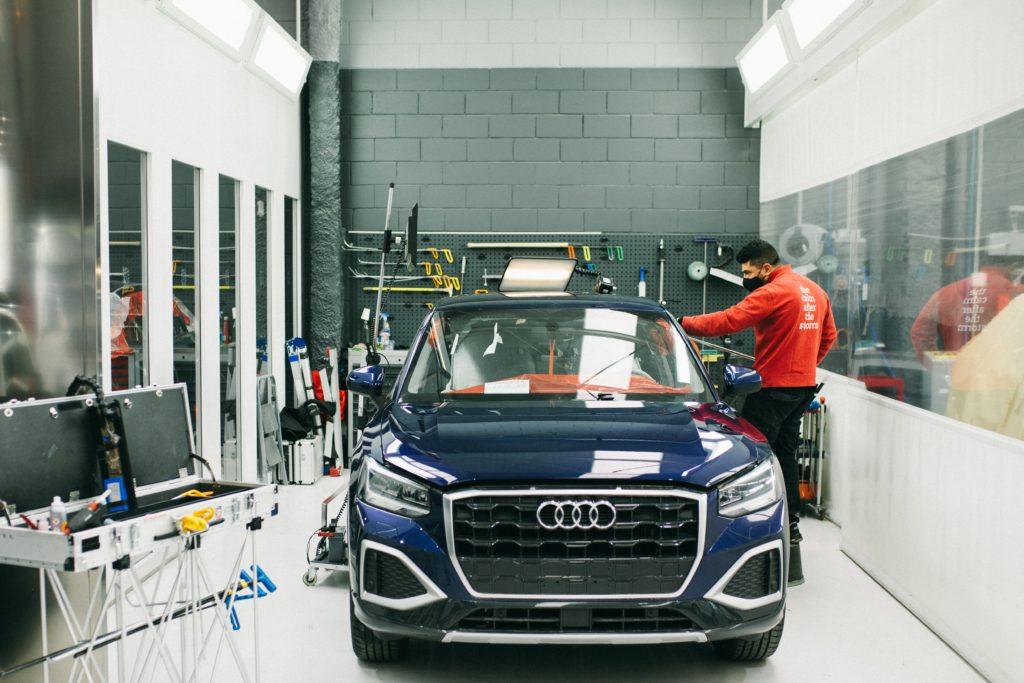 Un tecnico levabolli mentre ripara un'auto grandinata